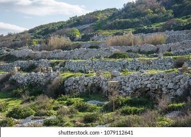 A small hill with Maltese rubble walls in Malta