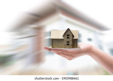 Small home model on hand white background,Hand holding wooden home model toy isolated on blurr home background,Real Estate Concept.