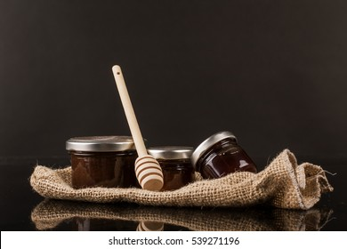 Small Honey jars on a black background