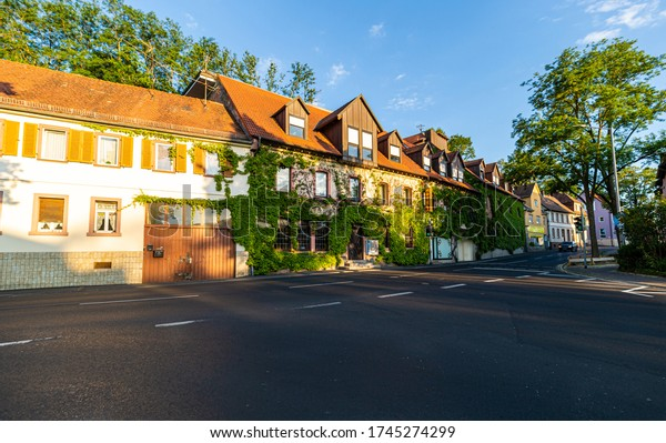 A small hotel on the street. House in the sun. The building is overgrown with ivy. Accommodation in Germany. Hotel in Bavaria. A quiet place.