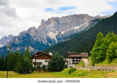 Small hotels, village road  and Dolomites view.