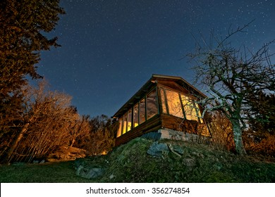 Small house with big orange windows and a bright starry night sky. Sweden