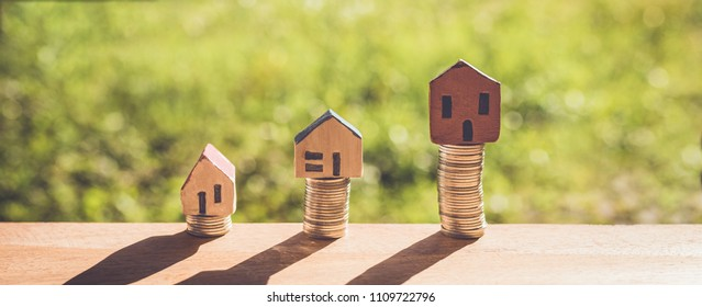 Small house with coins on green bokeh background. Home saving concept.