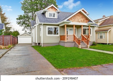 Small house exterior. View of entrance porch with walkway and garage with driveway