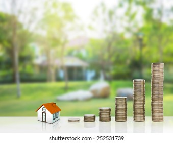 Small house and gold stack coins. The concept of purchase of habitation