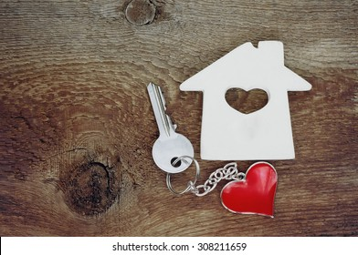 small house and a key with a key chain in shape of heart