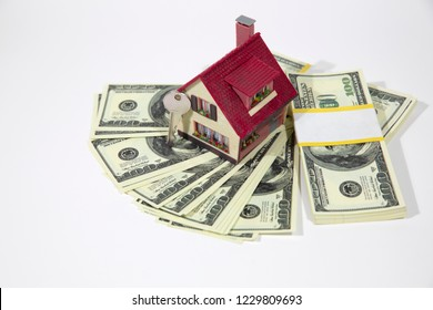 A small house lies on a fan of hundred dollar bills. The keys to the purchased house. Reduced copy of the house on a white background.