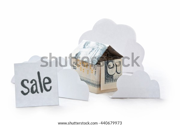 Small house made of dollar banknote isolated on white background. Inscription sale. Concept of real estate sale. Origami of money. Moneygami.