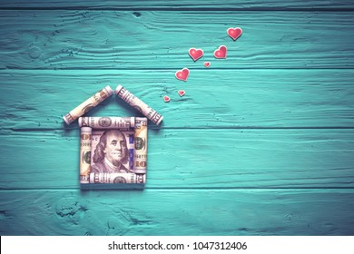 A small house made of money on a wooden table. Red hearts on wooden background. International currency.