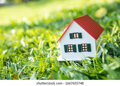a small house model on a green meadow