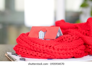 Small house model wrapped in red scarf