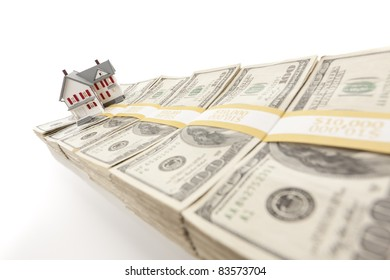 Small House on Row of Hundred Dollar Bill Stacks Isolated on a Gradated Background.