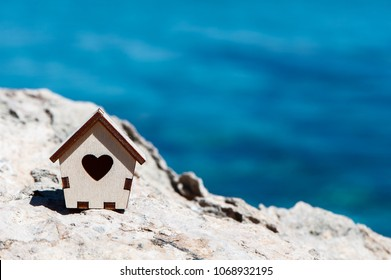 Small house on a stone on the background of the blue sea, space for text, the concept of a house by the sea, a summer holiday, life by the sea