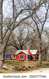 Small house with for sale sign in country among large trees with lawn mowers for sale and American and Confederate flags