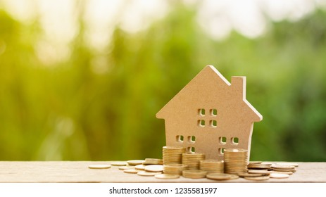 small house and a stack of golden coins in the garden. - Concept of Investment property.