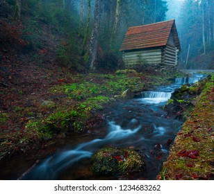 Small house stands on the banks of a mountain river. Foggy morning in the mountains