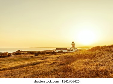 Small house in the sunset in Jeju Island, South Korea, on a golden meadow
