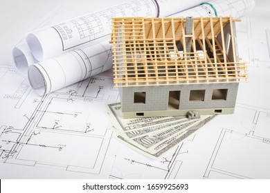 Small house under construction and currencies dollar on electrical drawings and diagrams for project, concept of building home cost