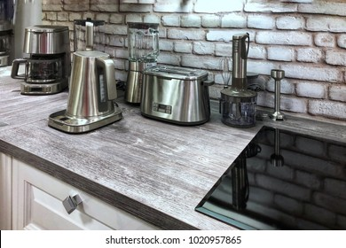 Small household appliances in the kitchen. Kitchenware in silver color on the table.