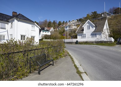 Small houses lays at a street in the old town of Drobak (Norway, Askershus) under a bright blue sky.