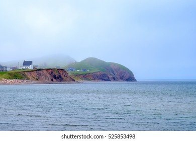 Small houses on grassy bluff with fog rolling in, Isle De Madeleine