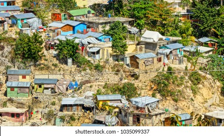 Small houses on a top of ruins left after earthquake on erosion ground on downhill. Haiti.