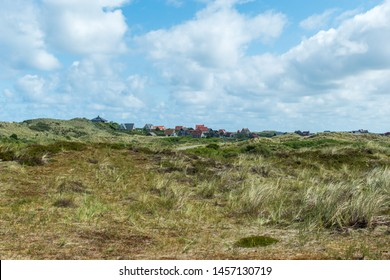 Small houses with red sloping roofs between the dunes with marram grass and cumulus clouds. Terschelling, The Netherlands, Europe.