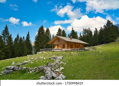 A small hut in the bavarian alps on a meadow with fresh green grass, some rocks and trees. Hiking in the karwendel mountain range on a sunny summer day, Germany.