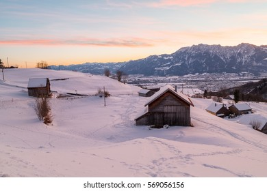 A small hut in front of a mountain covered in snow during the Swiss winter