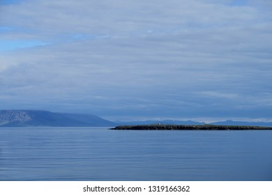 Small hut on distance island across calm blue sea, in West Fjords, Iceland