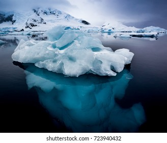 Small ice berg in clear, calm water showing turquoise ice underwater