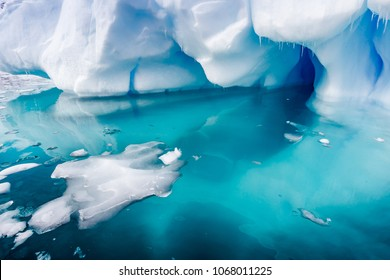 Small ice chunks float near a large iceberg surrrounded by torqu