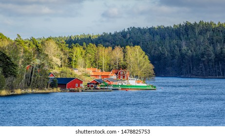 Small idyllic port in the swedish archipelago outside of Stockholm with moored coastal ro-ro ferry and earthmovers lighted with sunspot.