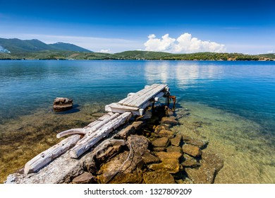 Small improvised boat jetty on the greek peninsula Pilion under a clear blue sky with some clouds