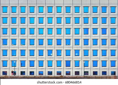 A small inconspicuous human walks along a tall building. Many windows on the facade of the building. Attacting litlle attention person.