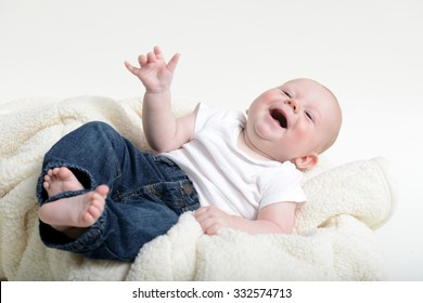 Small infant with a funny expression while laughing really hard and wearing jeans and a white shirt