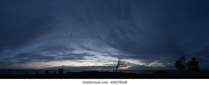 Small island in the Baltic Sea panorama. Single dead tree, sunset and stormy night on the beach. Mohni, Estonia, Europe.
