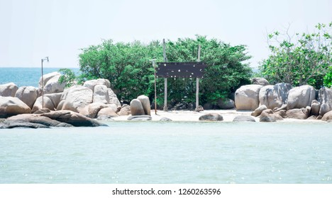 Small island with big rocks and wooden handmade blank sinage in a beach resort during a hot summer day