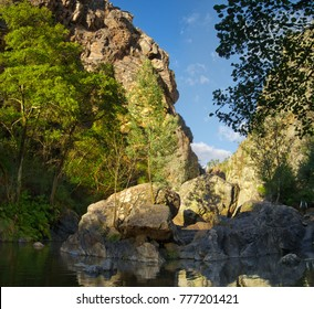 A Small island of eroded rocks and boulders in the middle of River Alge at Fragas de Sao Simao. Green trees and canyon cliffs on background. Figueiro dos Vinhos, Portugal.