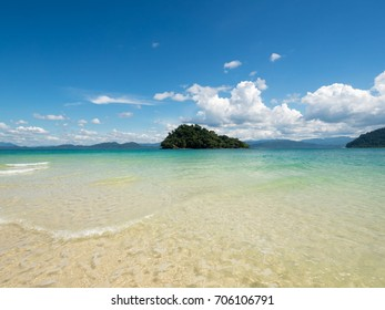 Small island filled with trees and rocky ground in the middle of emerald sea. Ranong, Thailand. The island is surrounded by sea and mountains with clouds in the blue sky.