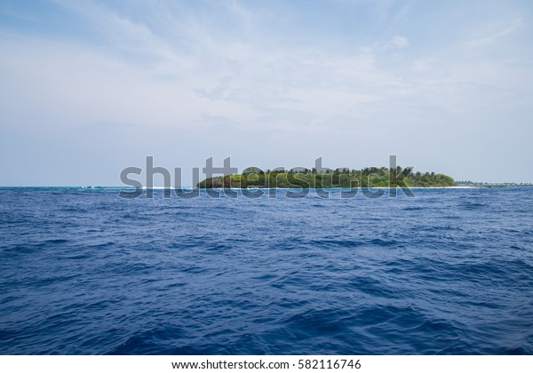 a small island in the Maldives seen from a boat with the blue Indian ocean in the foreground