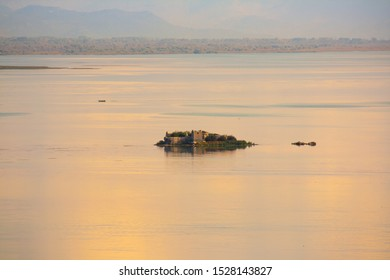 Small island with old castel in the middle of the cristal clear lake with reflection and sunset