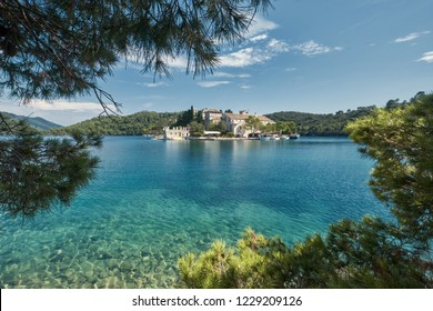 Small island on top of blue sea and sky surrounded by the forest. Saint Mary island inside Mljet National Park in Croatia.