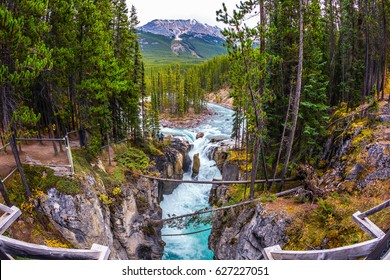 Small island in the river. The waterfall rushes to the rocky shores. Jasper National Park, Canada. The concept of extreme and ecological tourism