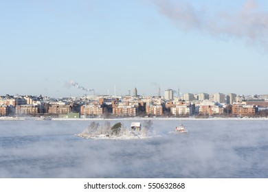 Small island in a steaming sea in Helsinki, Finland at winter