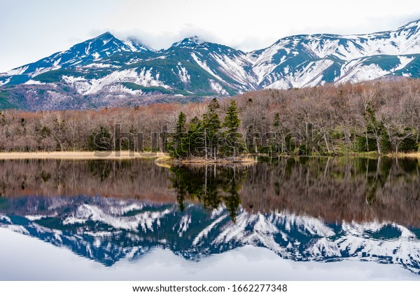 Small islet in the lake, beautiful lake surface reflecting blue sky like a mirror, rolling mountain range and woodland in the background on springtime sunny day. High latitude country natural scenery