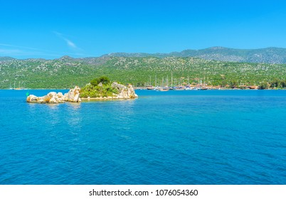 The small islets in Kekova bay with preserved ancient ruins of Lycian settlements and yachts in Ucagiz harbor on the background, Turkey.