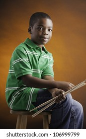 A small isolated African American male child  in a green shirt sitting on a wood stool holding drumsticks and smiling against an orange background.