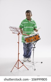 A small isolated African American male child in a green shirt studying how to play a snare drum against a white background.