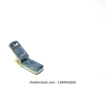 Small isolated, silver metal flip cell phone closeup. Bringing awareness to distracted driving, feeling hopeless, depression, domestic violence, suicide and isolation.